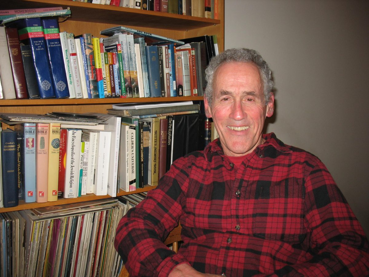Professor Joe Butwin smiles in his office, seated in front of a bookshelf full of books