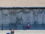 Child standing near the Berlin Wall. Photo via Flickr.