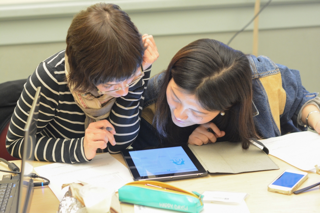 Katja Schatte and Dawn Yang use a tablet to view a Jewish ritual text.