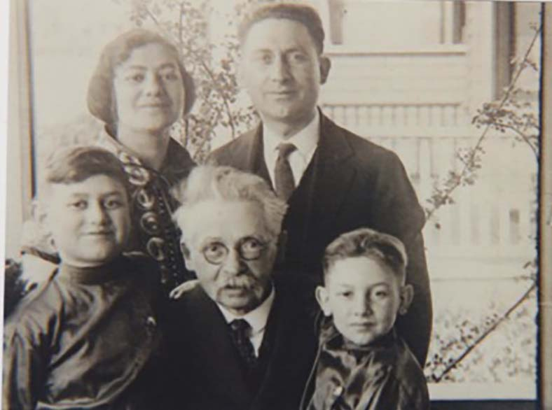 The Susman family dressed in Russian-style fine clothing, gathered around Zaybe Winchevsky