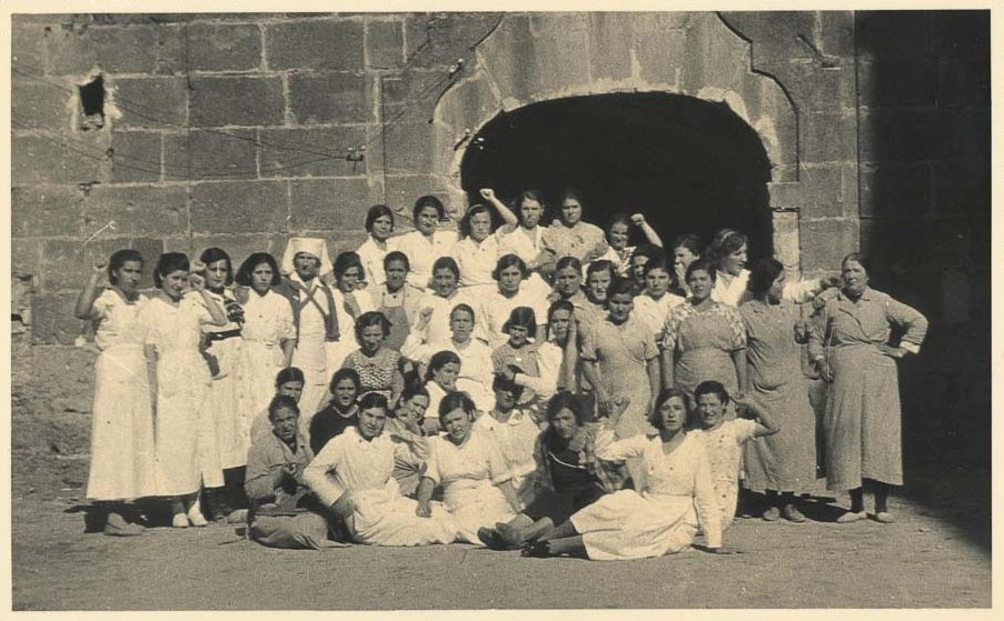 Around thirty women in white stand in front of a stone hospital