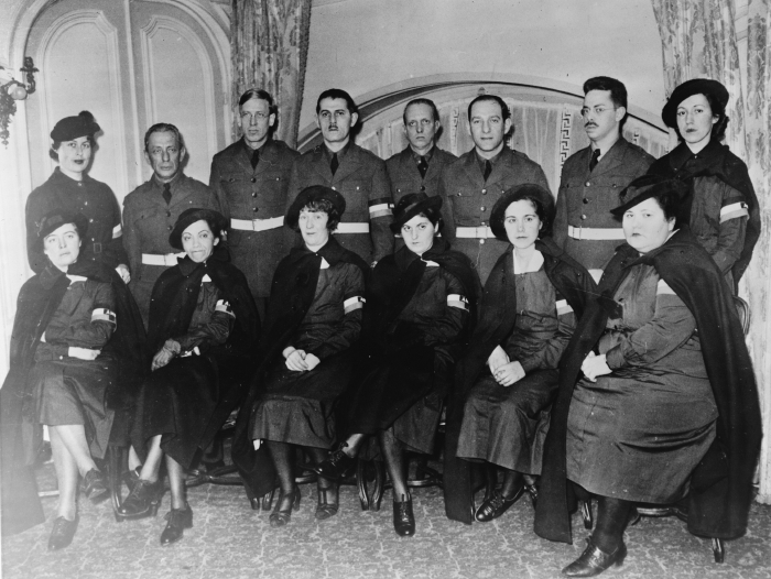 Somber-looking doctors and nurses in matching uniforms pose for a photograph