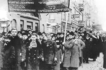Workers march down the street carrying a banner covered with Yiddish slogans