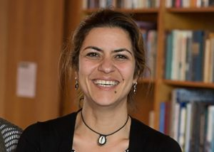 Picture Hadar Khazzam-Horovitz smiling, wearing a sweater, necklace and earrings, with bookshelves in the background