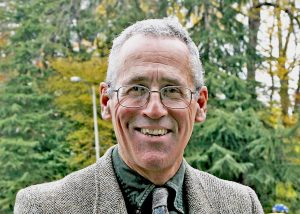 Joe Butwin smiles at the camera in suit and glasses, in front of trees