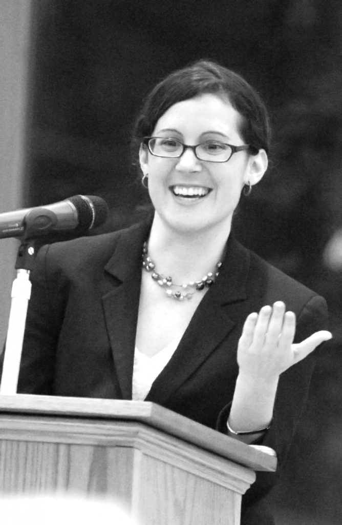 Black-and-white portrait of Professor Ahuvia delivering a lecture at a podium, smiling, wearing a blazer