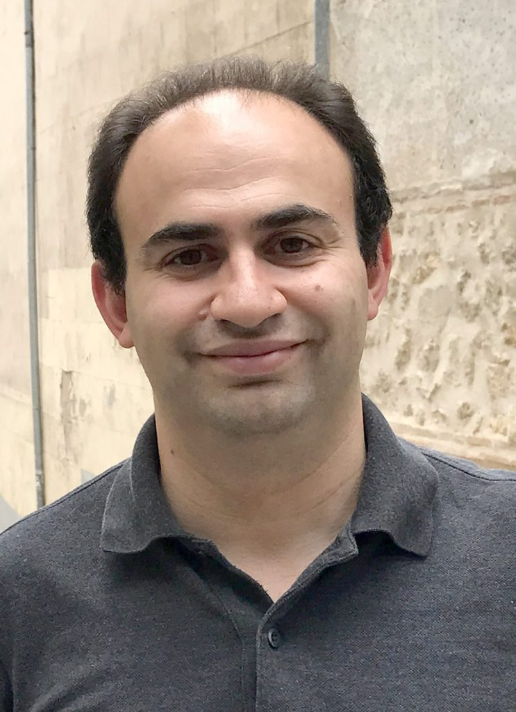 Portrait of Sasha Senderovich, smiling, wearing a button-up short-sleeved gray shirt, with a European streetway of light stone behind him