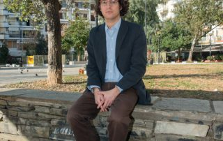 Devin Naar sitting near broken Jewish tombstones used as building materials in Salonica
