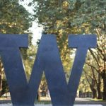 "Photo of bronze sculpture of a ""W"" at an entrance to the University of Washington. Leafy trees are visible in the background."