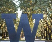 """Photo of bronze sculpture of a """"W"""" at an entrance to the University of Washington. Leafy trees are visible in the background."""
