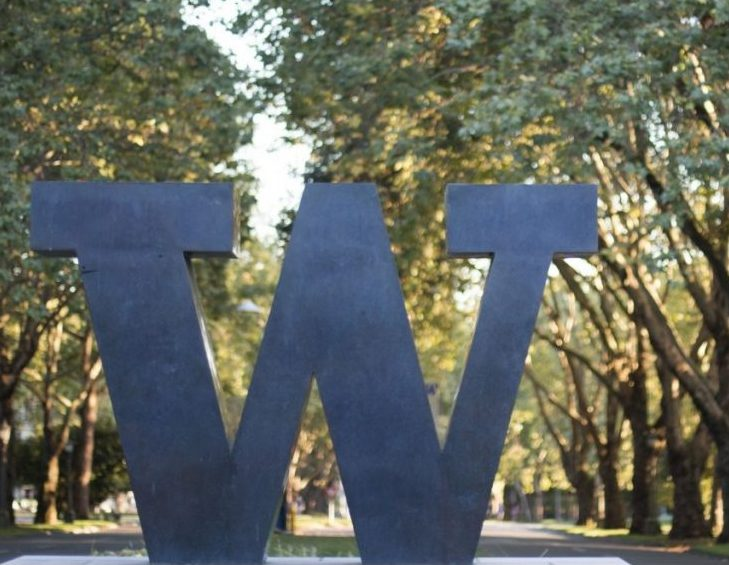 "The bronze ""W"" sculpture standing at the front of one of the University of Washington campus entrances, with trees in the background."