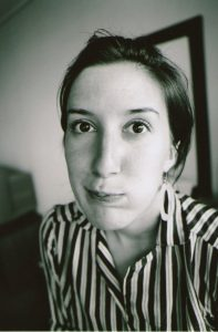 Black-and-white portrait of Denise wearing a striped blouse, hair back, with a bemused expression