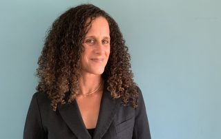 Portrait of Sarah Aberevaya Stein wearing a blazer, smiling, standing against a blue wall