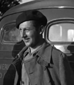A young Bill Susman wearing a beret and standing in front of a car