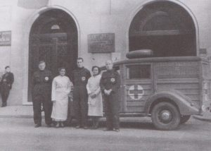 Medical staff stand at the side of an ambulance