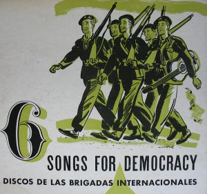 """Cover showing a smiling group of marching soldiers, one carrying a guitar. """"6 Songs for Democracy: Discos de las Brigadas Internacionales"""""""
