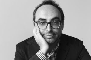Portrait of Gary Shteyngart wearing glasses, cheek in hand