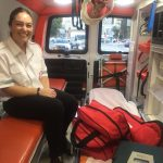 Tess Seltzer rides in the back of an ambulance in a white and black medical uniform, medical equipment in bags at her feet.