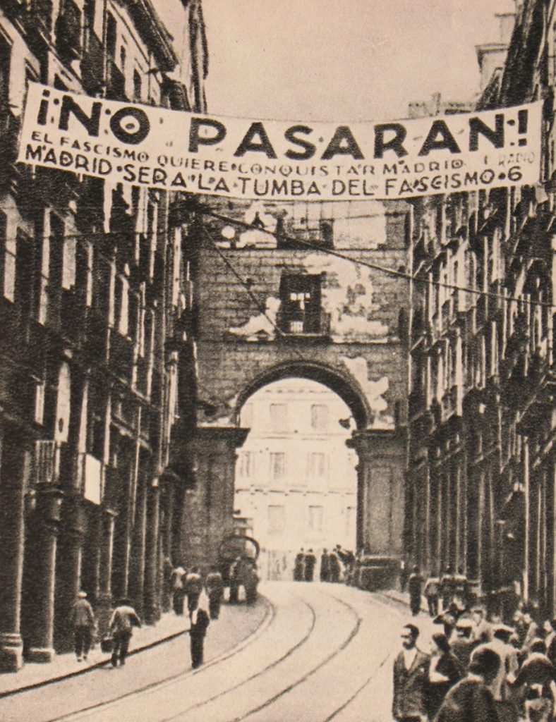 An anti-fascist banner hangs above an ancient bridge and arterial in Madrid
