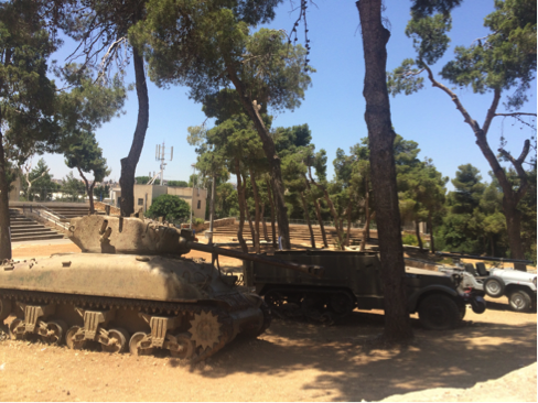 An old tank next to military vehicles under trees
