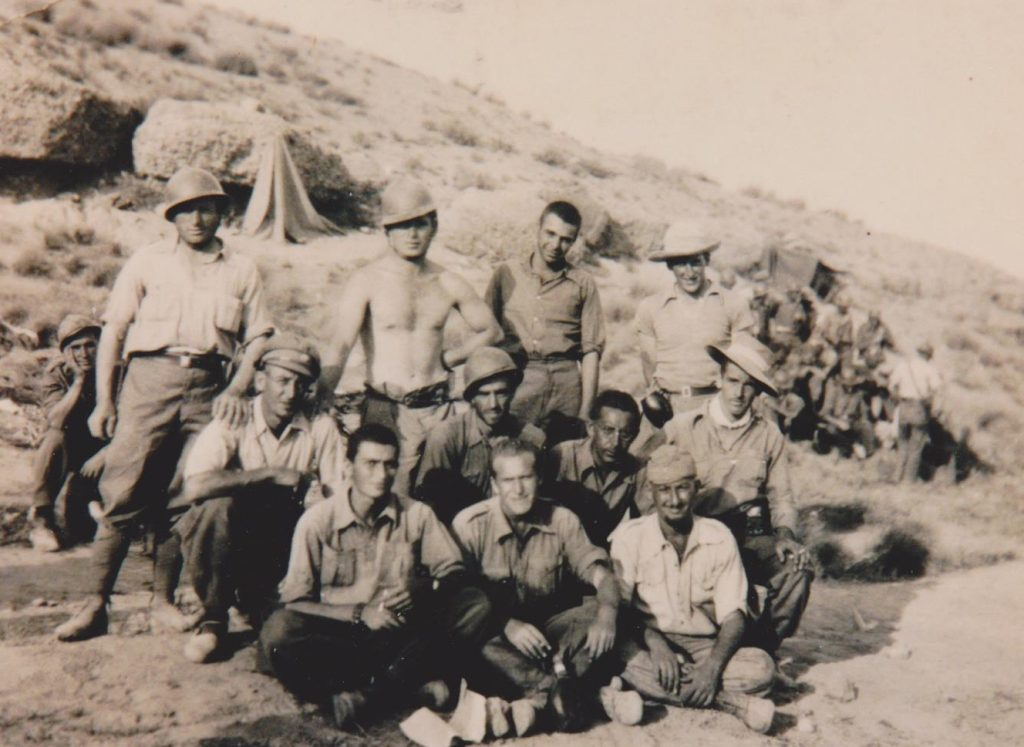 A group of informally dressed soldiers, some wearing helmets, poses for a photo in front of their hillside encampment