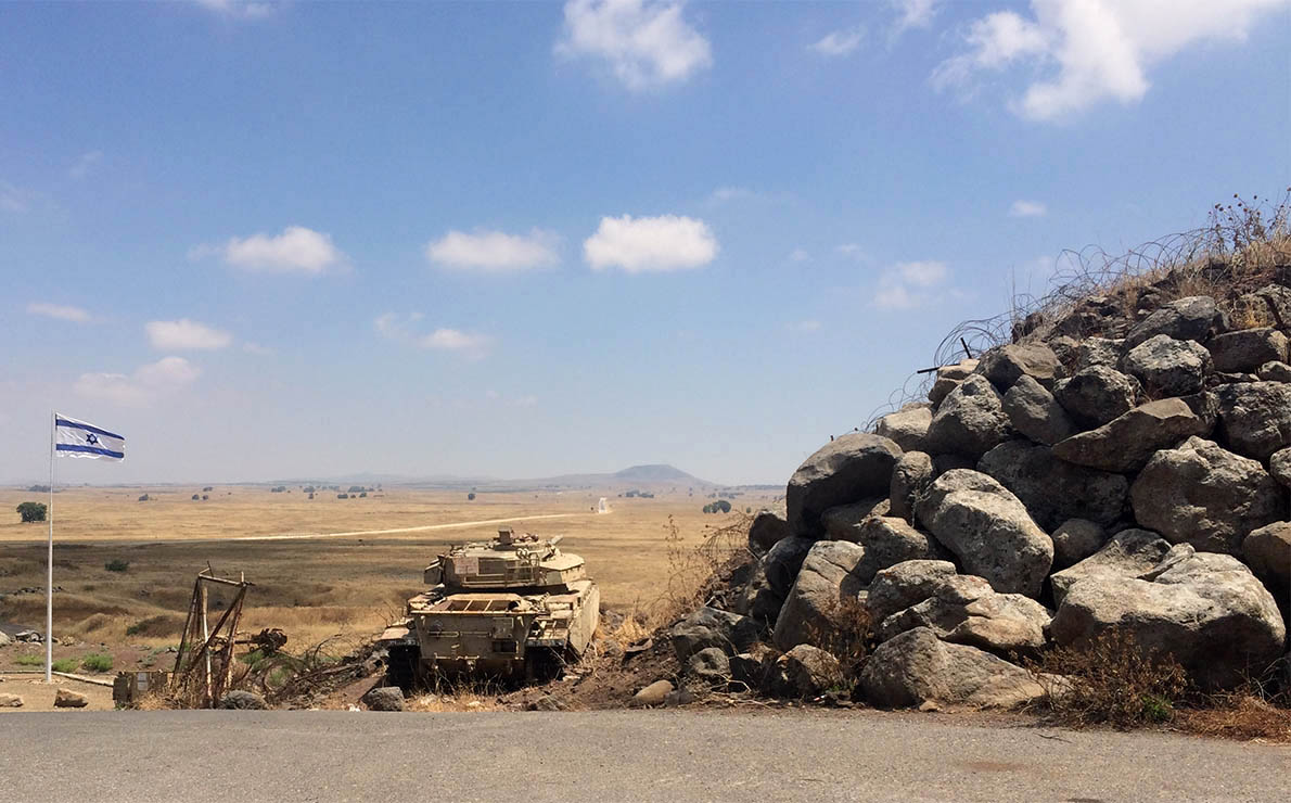 An old tank pointing at the horizon sits next to a barricade and an Israeli flag