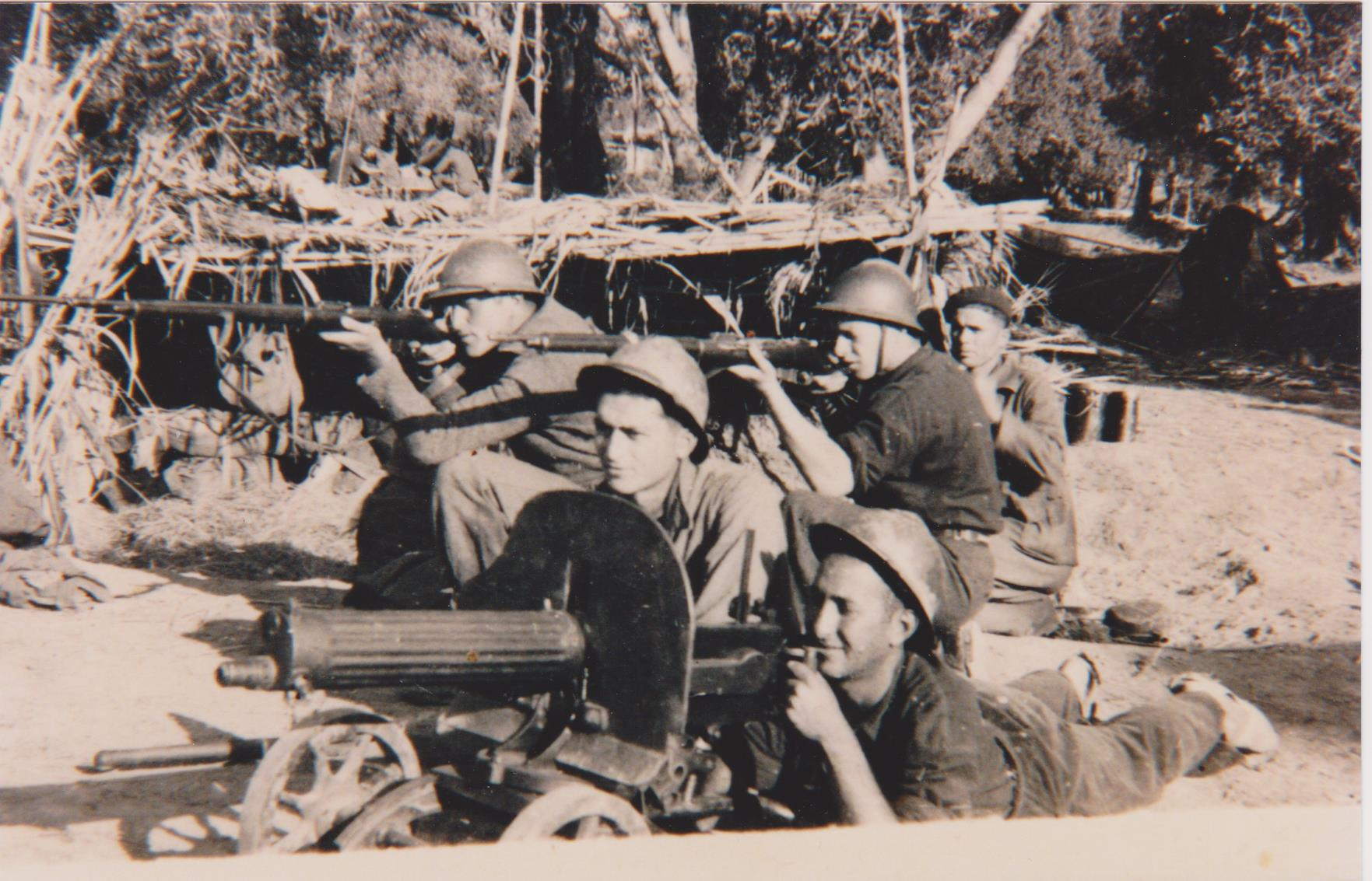 Soldiers in uniform aim rifles and man artillery