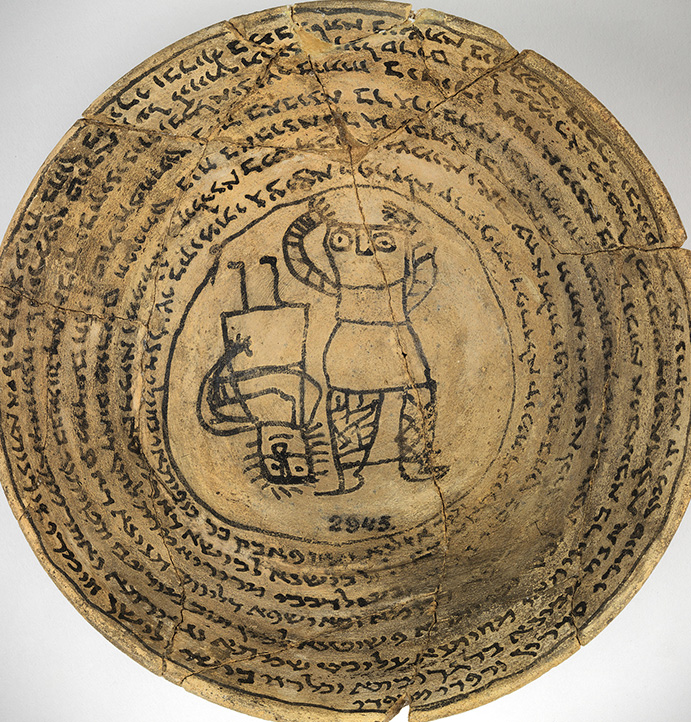 Overhead photo of the interior of an ancient terracotta bowl, ringed with Hebrew inscriptions and with two rudimentary human-like figures at the base