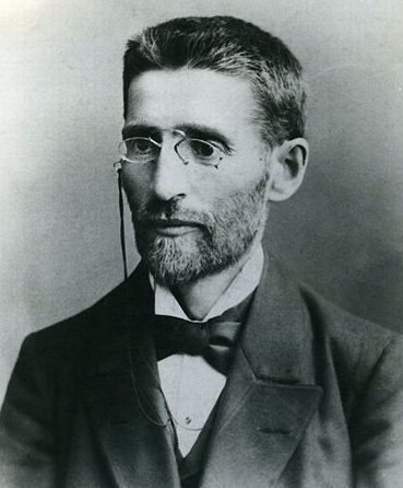 Black and white photo portrait of Ben Yehuda, wearing a suit, tie and glasses
