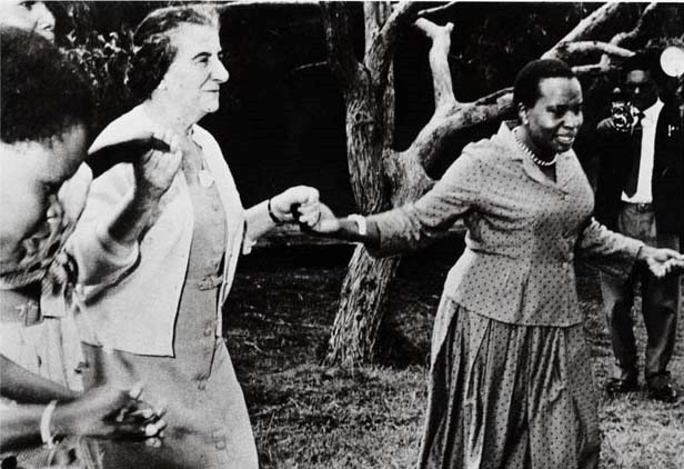 Golda Meir in dress and sweater holds hands with Jomo Kenyatta, who wears a two-piece dress
