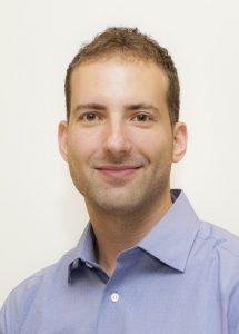 Portait of Bryan Kirschen, smiling, with short-cut hair, wearing a button-up shirt