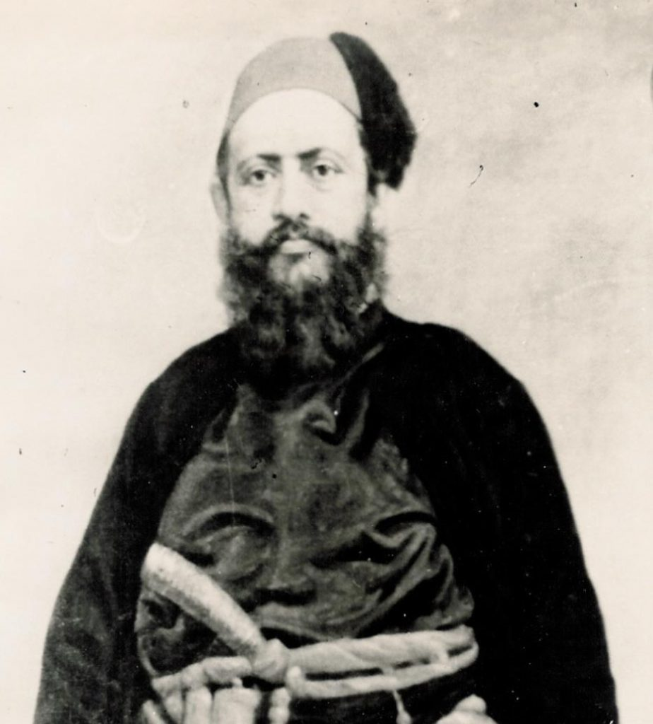 A black and white historic photo of Hataria, who wears heavy traditional clothing, wears a fez, and has a long beard