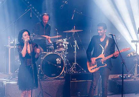 Ninet Tayeb sings into a mic and Dudu Tassa plays guitar onstage in a live concert photo