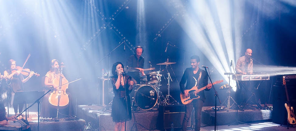 This live concert photo shows a glamorous Ninet in black dress singing into a mic, with Dudu in black business-casual garb playing guitar next to her