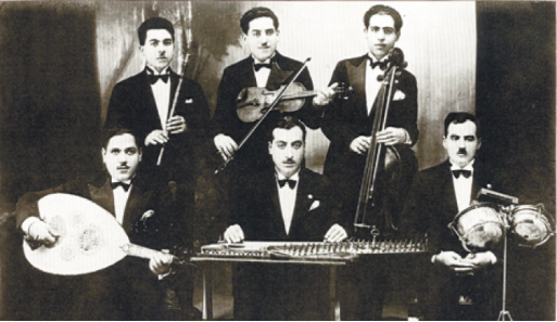 A historic photograph of a group of mustachioed musicians in suits, holding a combination of Western and traditional instruments