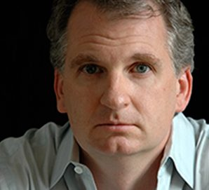 Portrait photograph of a serious-looking Snyder in an open collared shirt