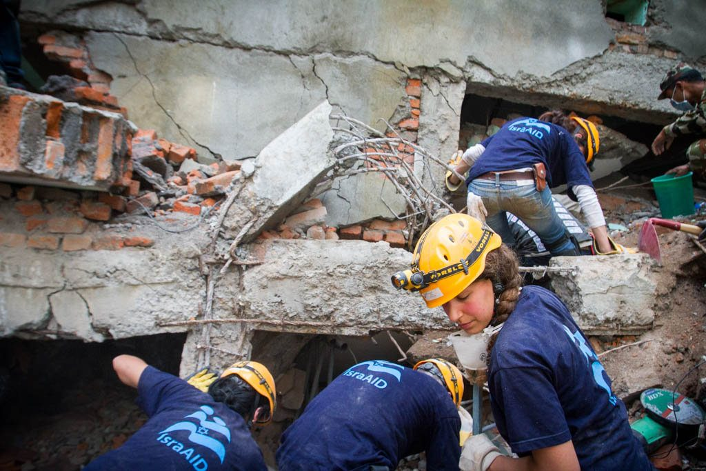 Workers in T-shits, jeans, and hard hats clearing a collapsed building