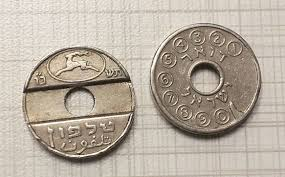 Two silver pay-phone tokens, adorned with the Postal Company deer logo, Hebrew, Arabic, and numbers, with holes in the center