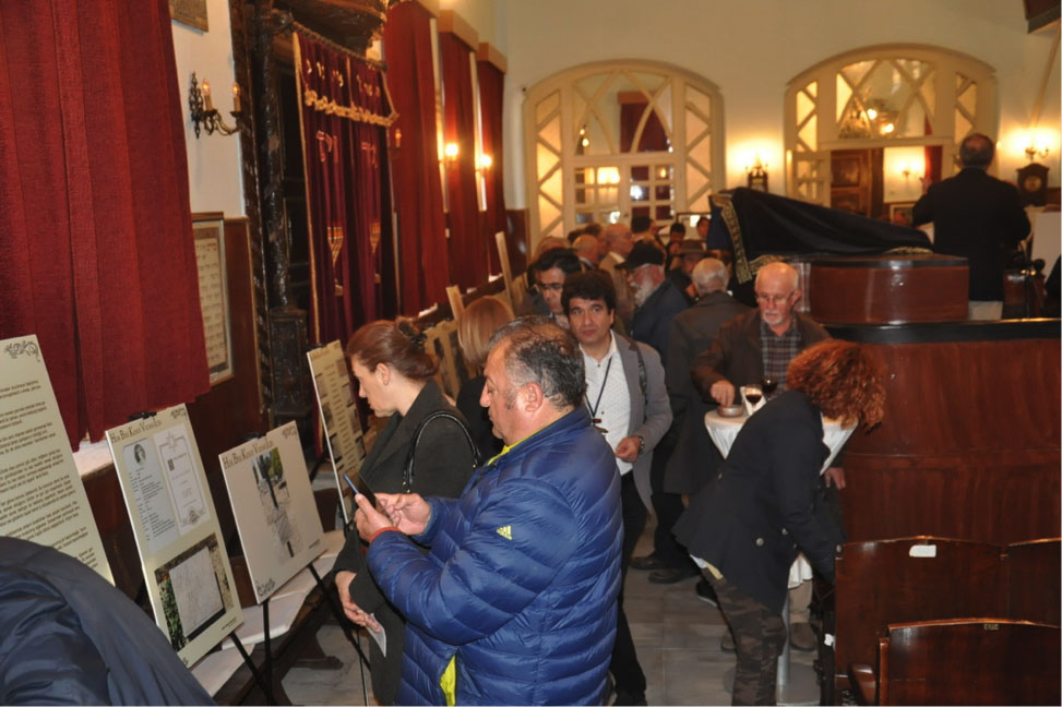 Attendees walk through the exhibit, looking at panels, in a synagogue with mahogany seats and crimson curtains