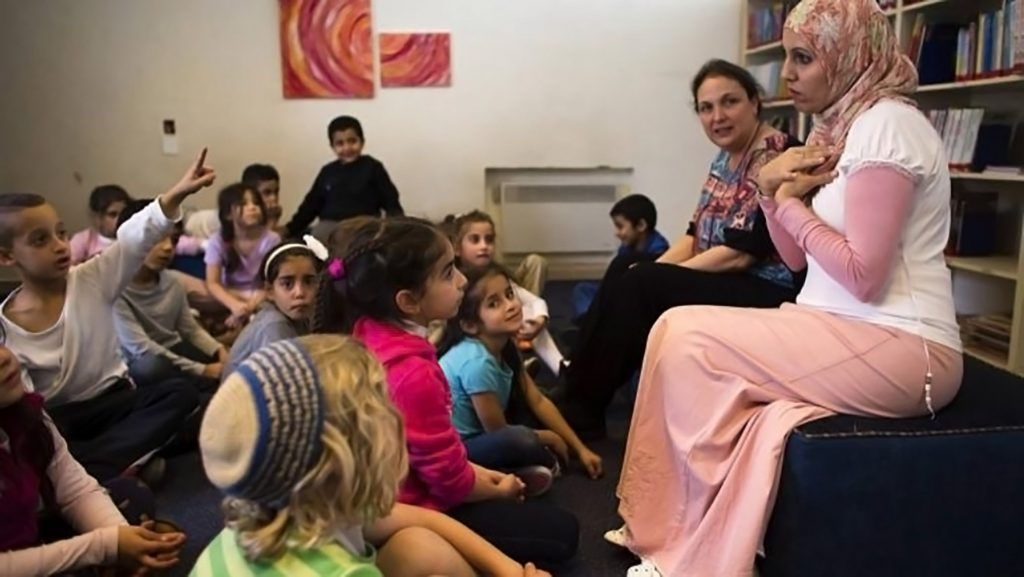 A mix of Arab and Jewish children sit listening to a woman in a pink hijab