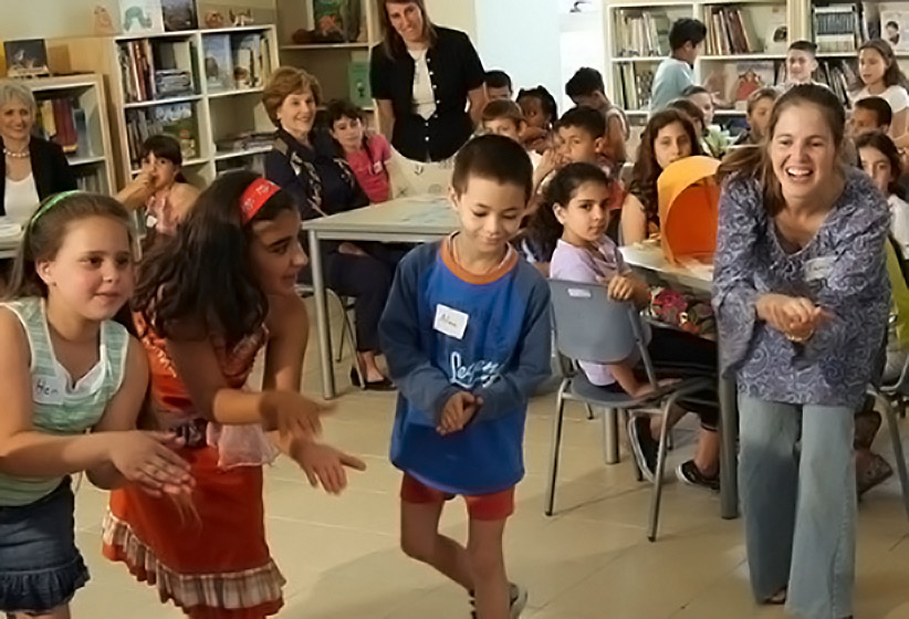 Students perform a circular dance with clapping in a classroom as their peers look on