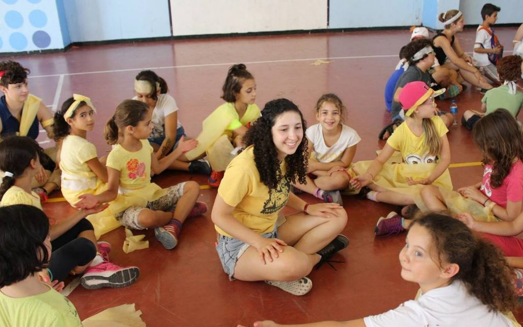A group of girls in yellow summer camp T-shirts sit in a circle around an energetic camp counselor