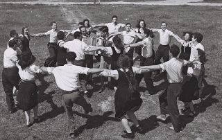 A black and white photograph shows a group of young people dancing the hora in two rings, around accordion-playing musicians on a field