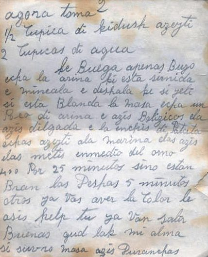 "A handwritten recipe written in cursive in pencil, calling for ""1/2 cupica di kidush azeyti"" and ""2 cupicas di agua"""