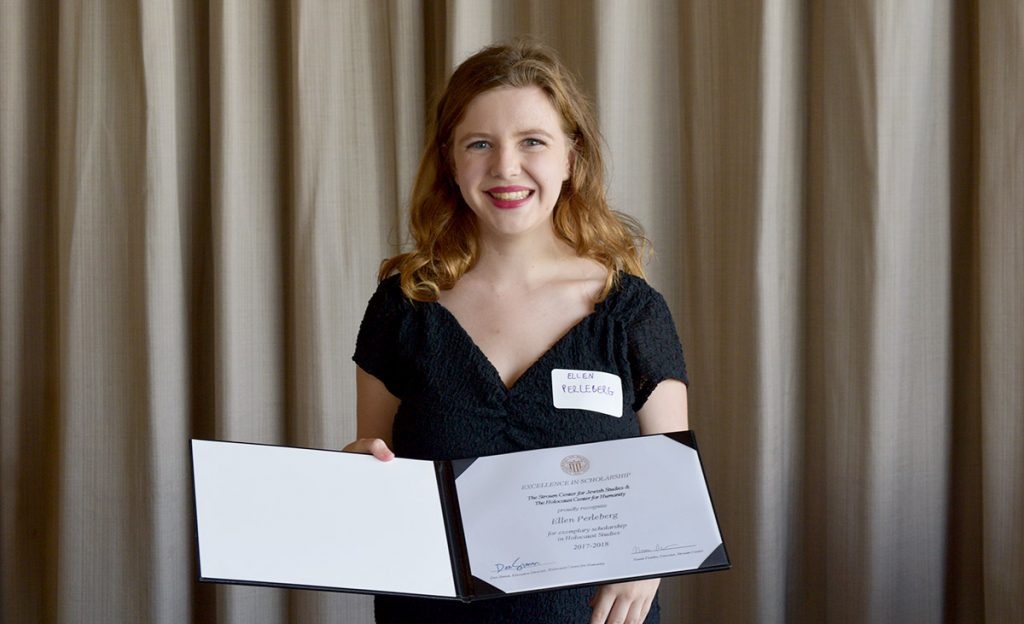 Ellen, wearing a formal black dress, smiles and shows a certificate to the camera