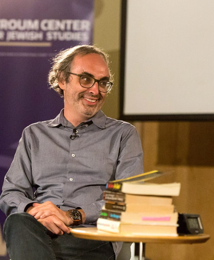 Gary Shteyngart smiles, a stack of books in front of him