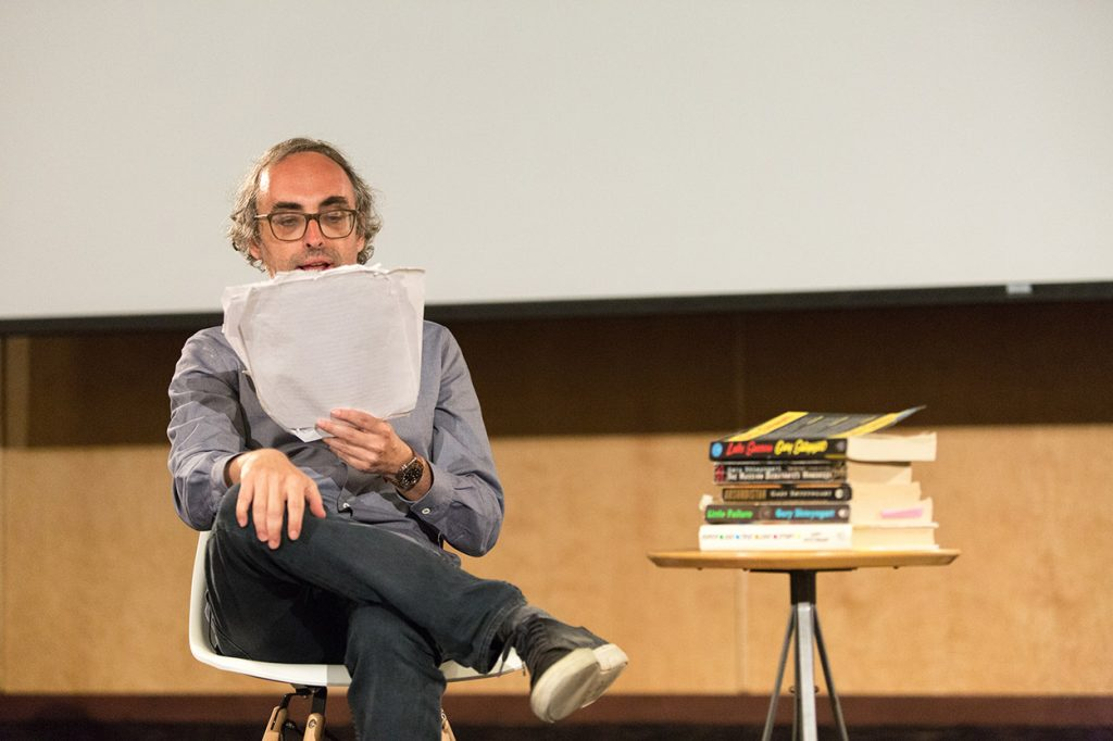 Seated in a chair next to a table stacked with his books, Shteyngart reads from a stack of papers