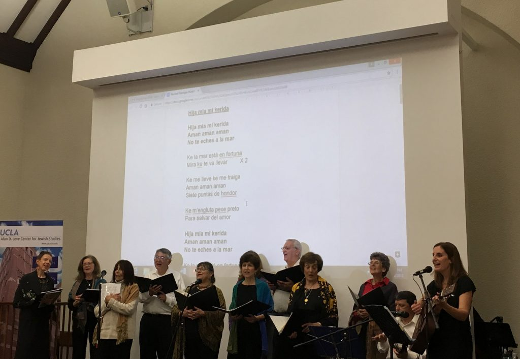 "An assembly of singers performs at the front of the room, accompanied by a guitarist, lyrics to ""Hija mia mi kerida"" projected behind them"