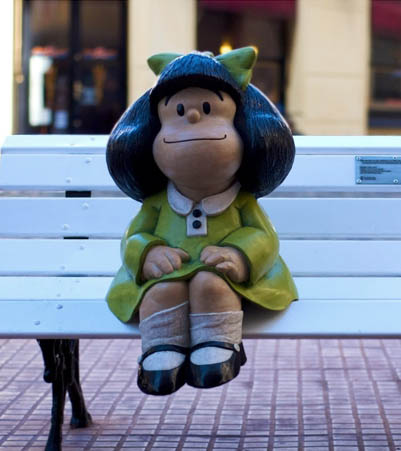 A child-sized color statue of the comic character Mafalda seated on a bench in a public square