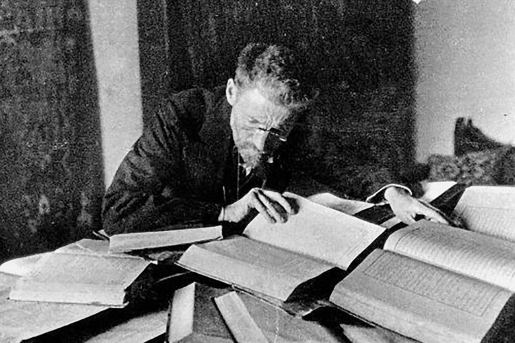 Black-and-white photograph of Ben Yehuda leaning, in glasses with short hair, leaning close over a book stacked on top of a large pile of books